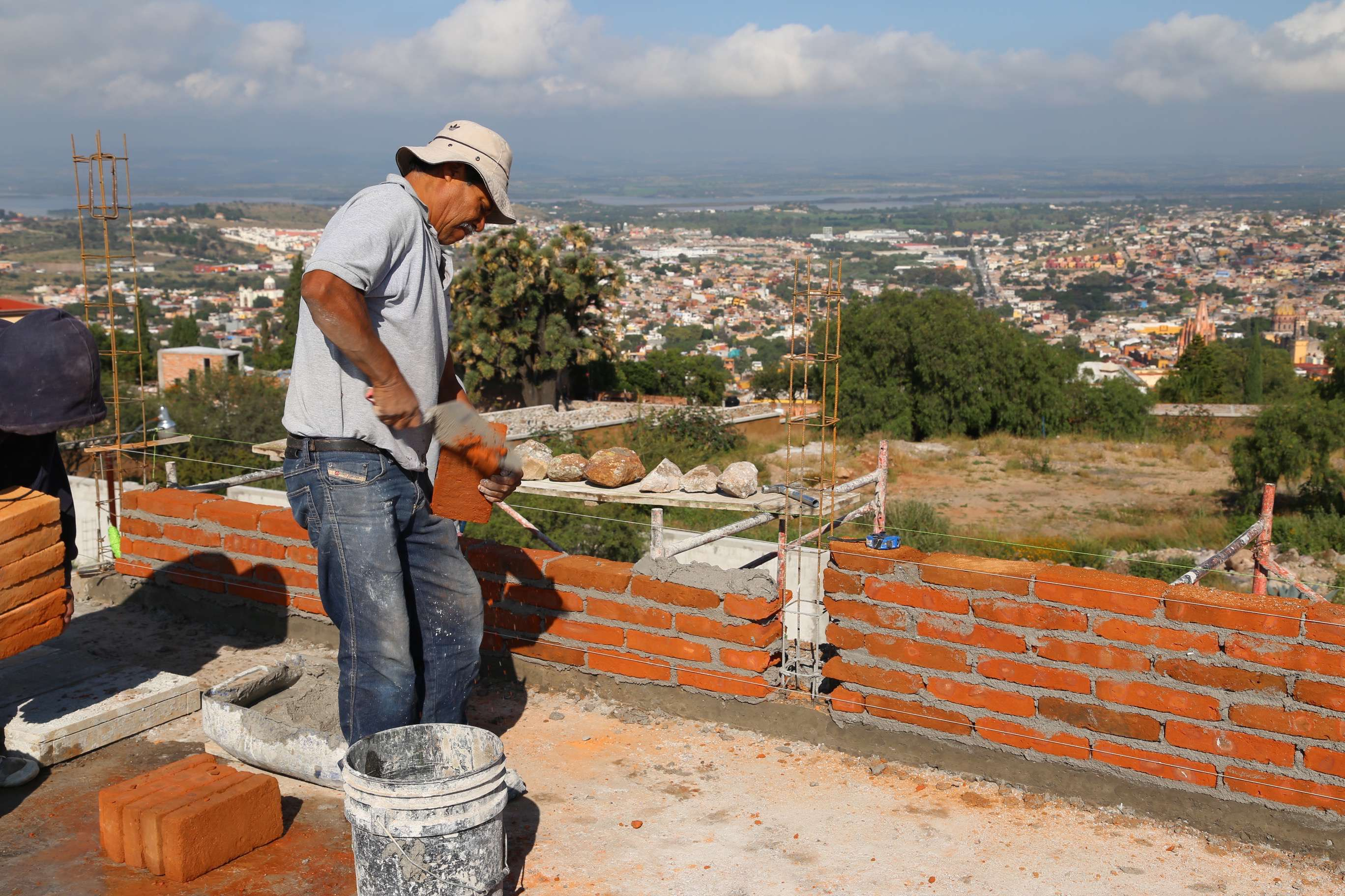 A mason deftly trims off a brick during the construction of a new home high in the hills.