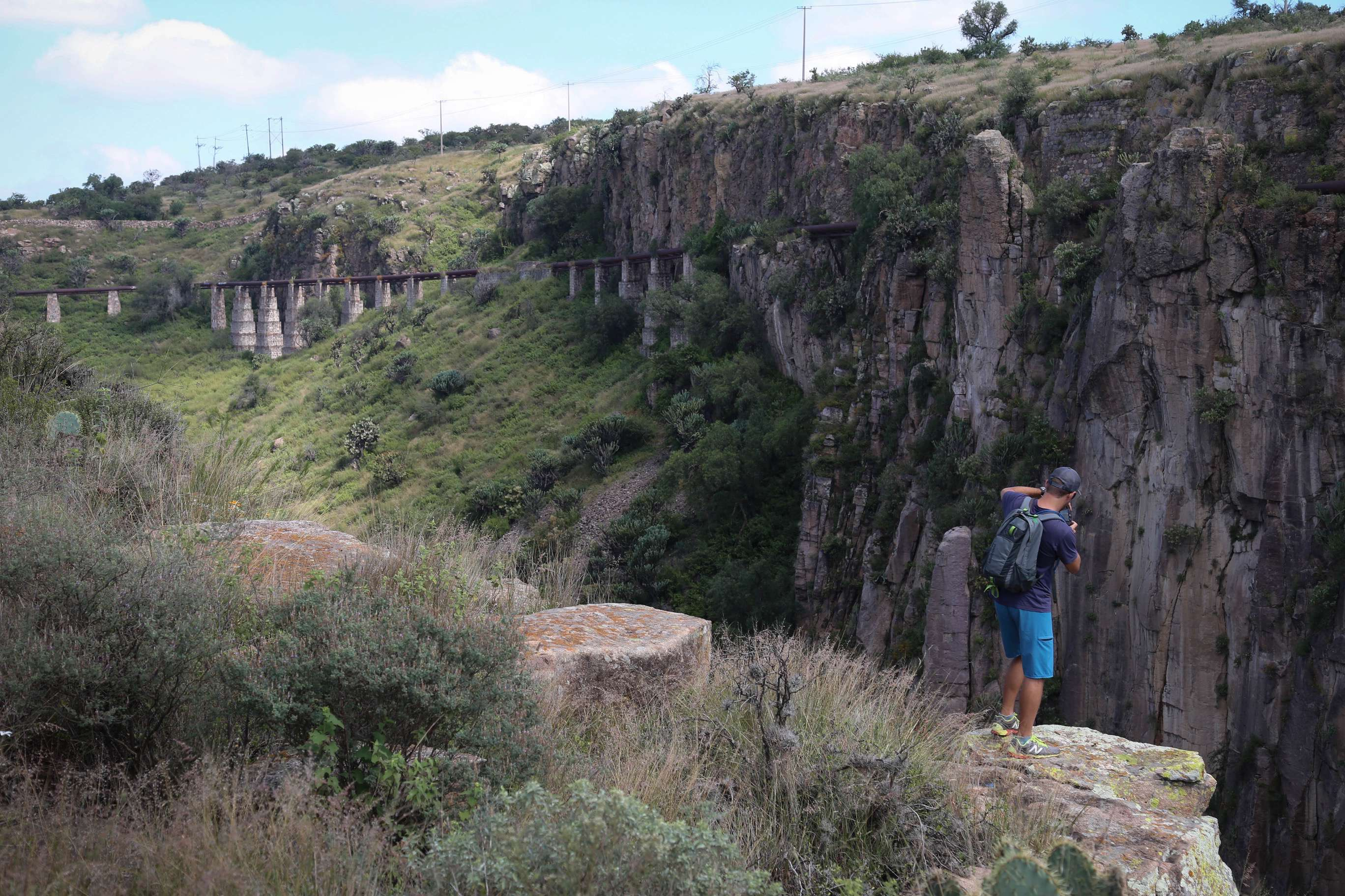 A visitor ventures out for a shot of the canyon below. The aqueduct in the distance carried water to the now-reuprposed factory in San Miguel de Allende.