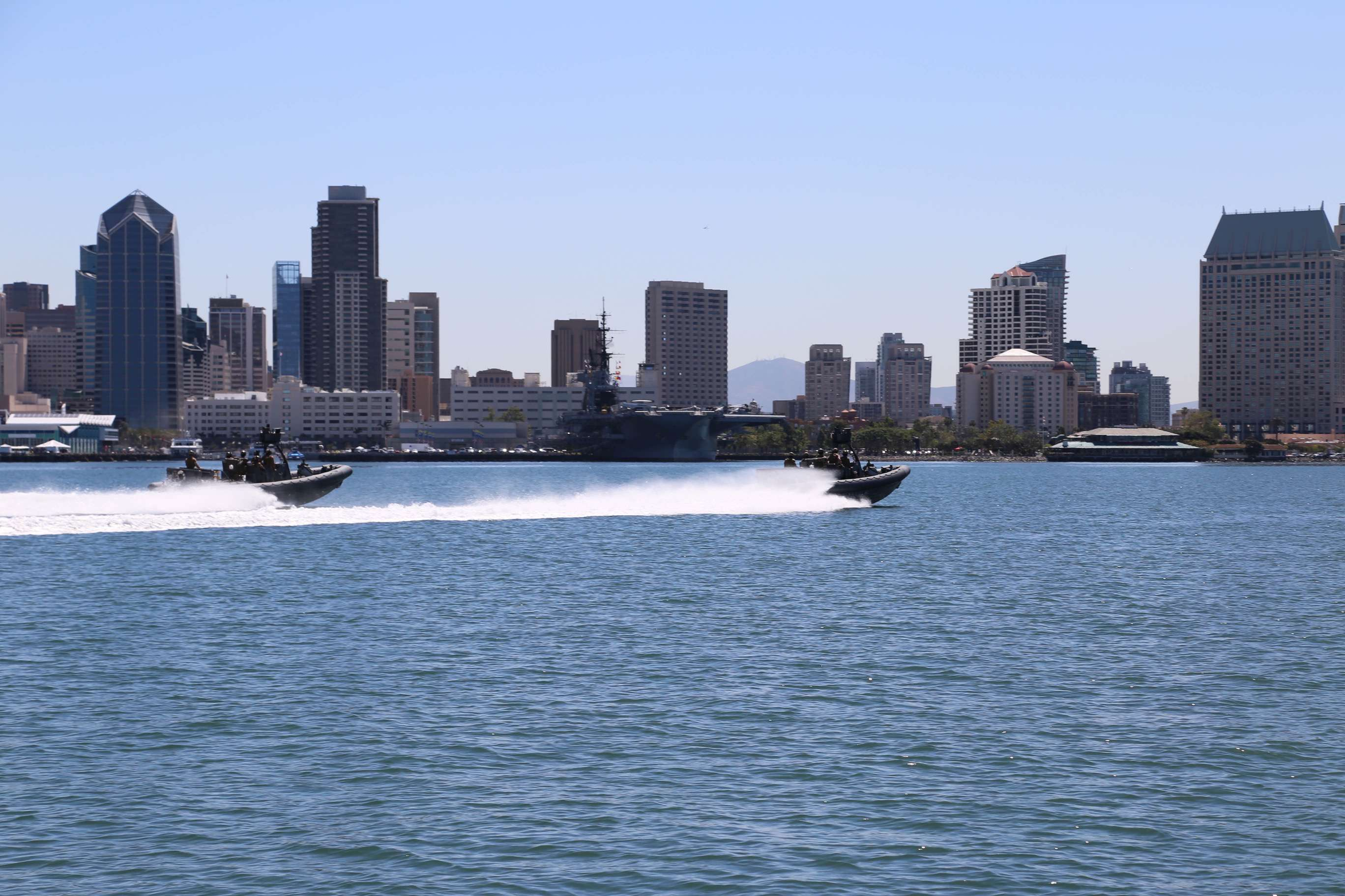 A pair of swift boats load with U.S. Navy Seals scoots past the San Diego harbor.