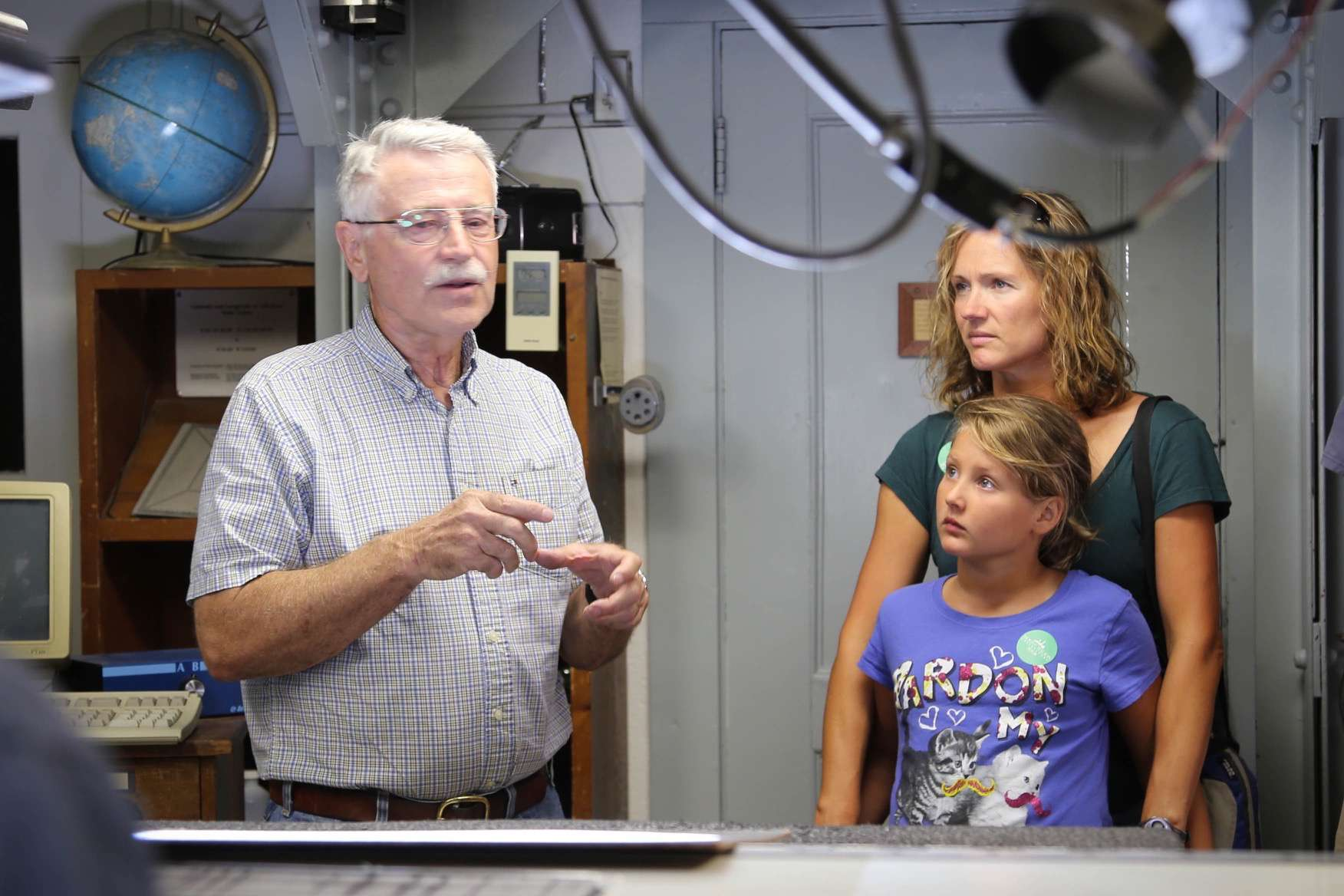 A young girl and her mother listen attentively as one of the observatory staff members explains how things work.