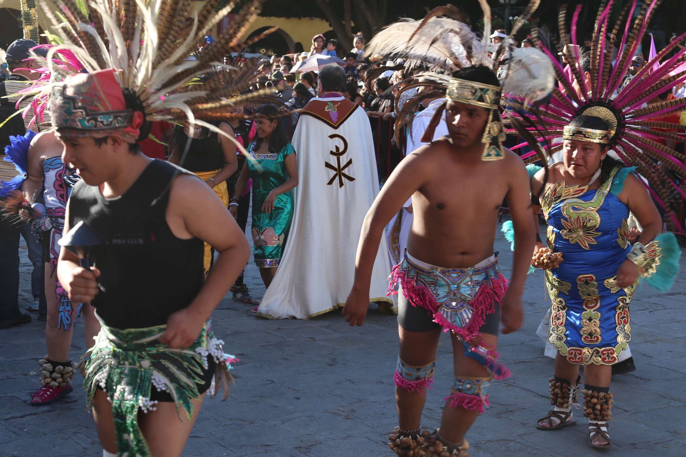 Mexico has many beliefs and they combine at times like these when a Catholic priest wades into a crowd of parade performers.