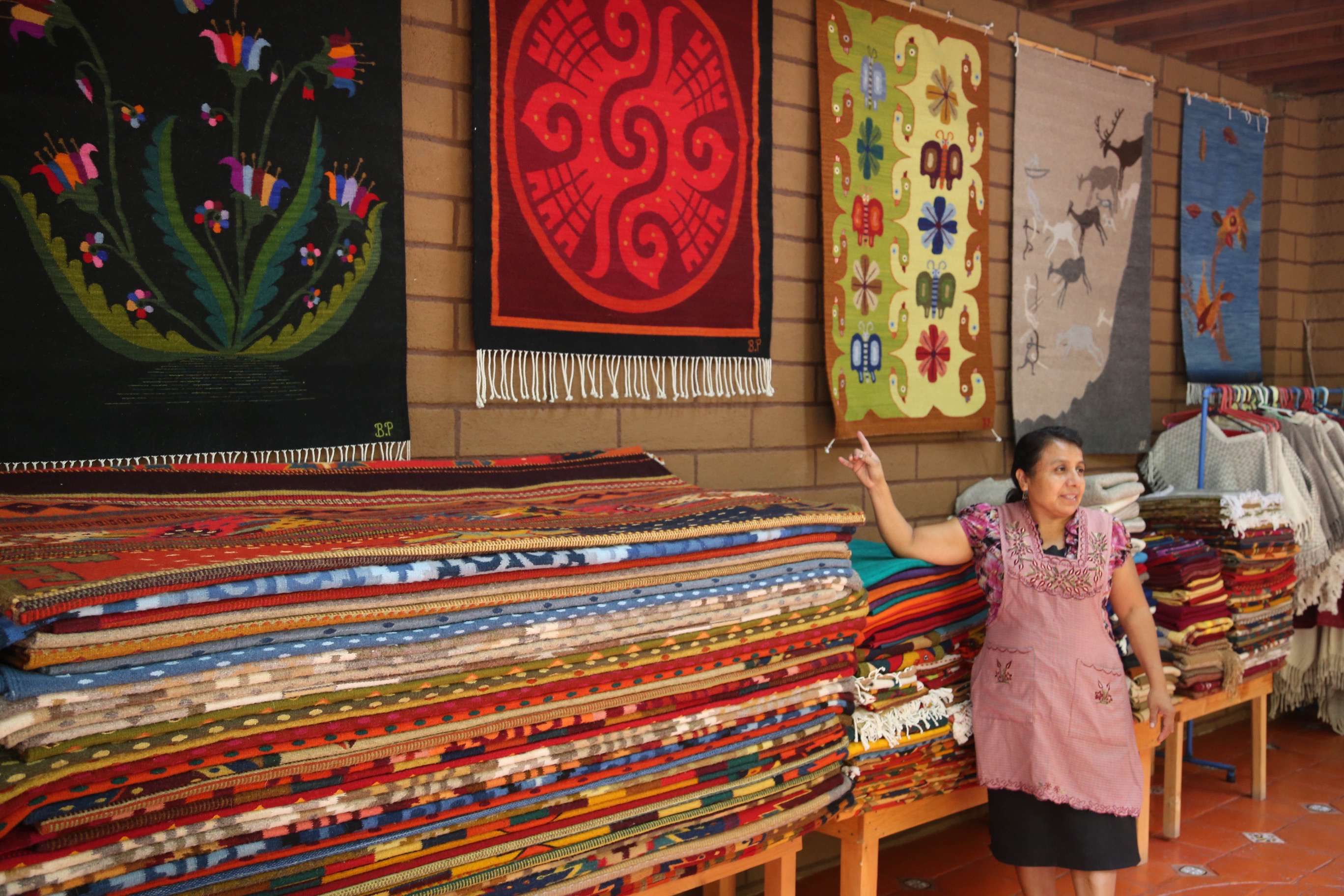 Felipa Lazo De Lopez Points To The Many Rugs Offered For At Her