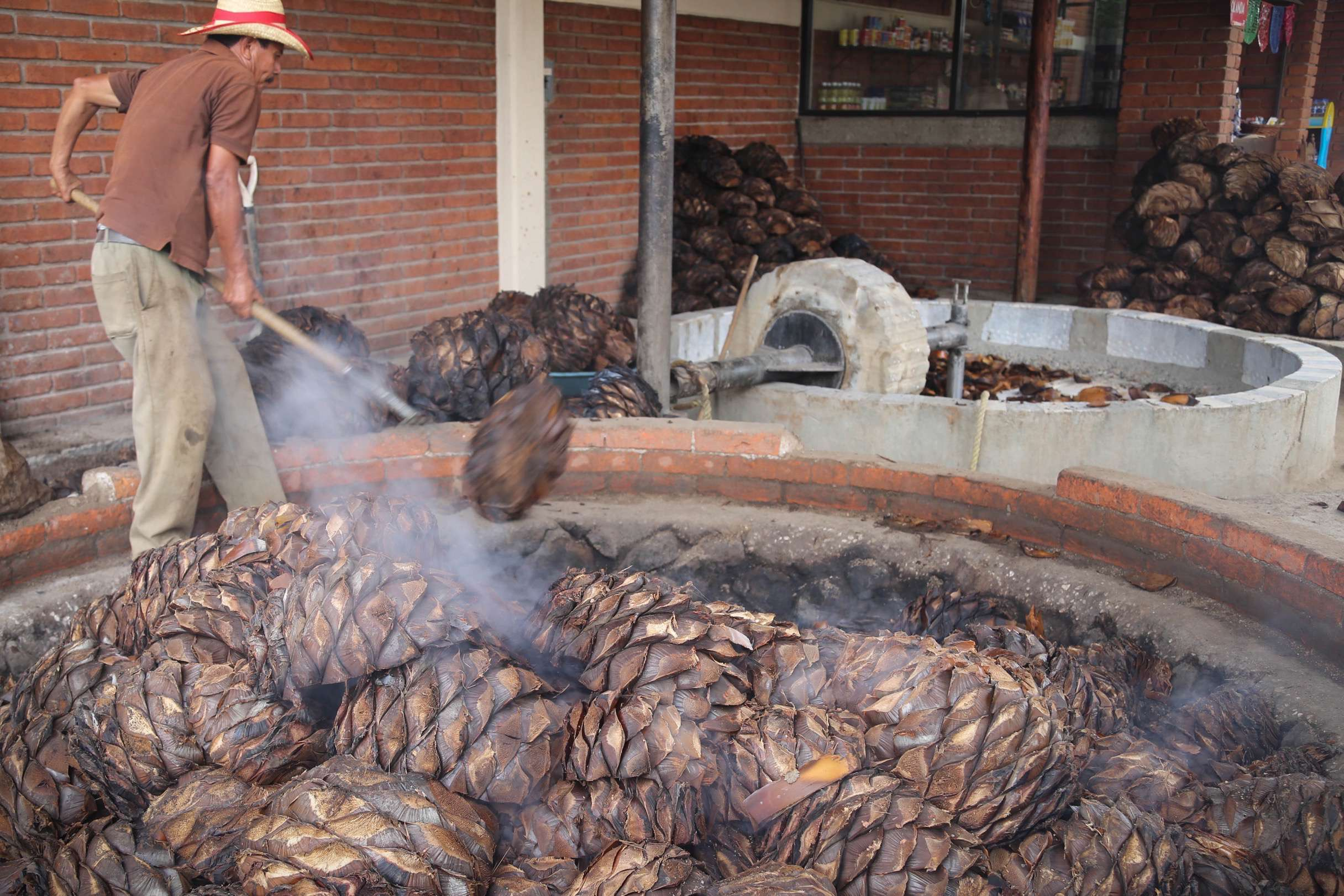 To make a proper mezcal, piñas are roasted under watchful eyes.