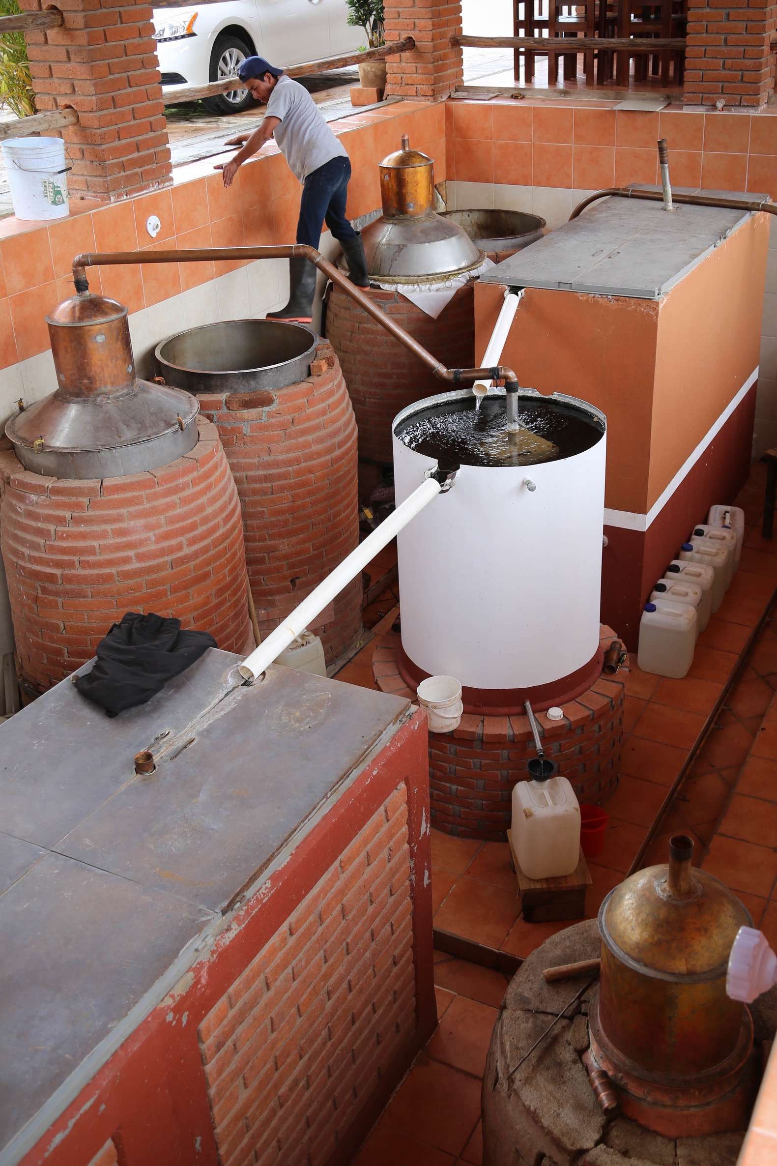 The copper pot still on the left, is producing mezcal that courses through the cooling tube and is collected in the white jug at the bottom.