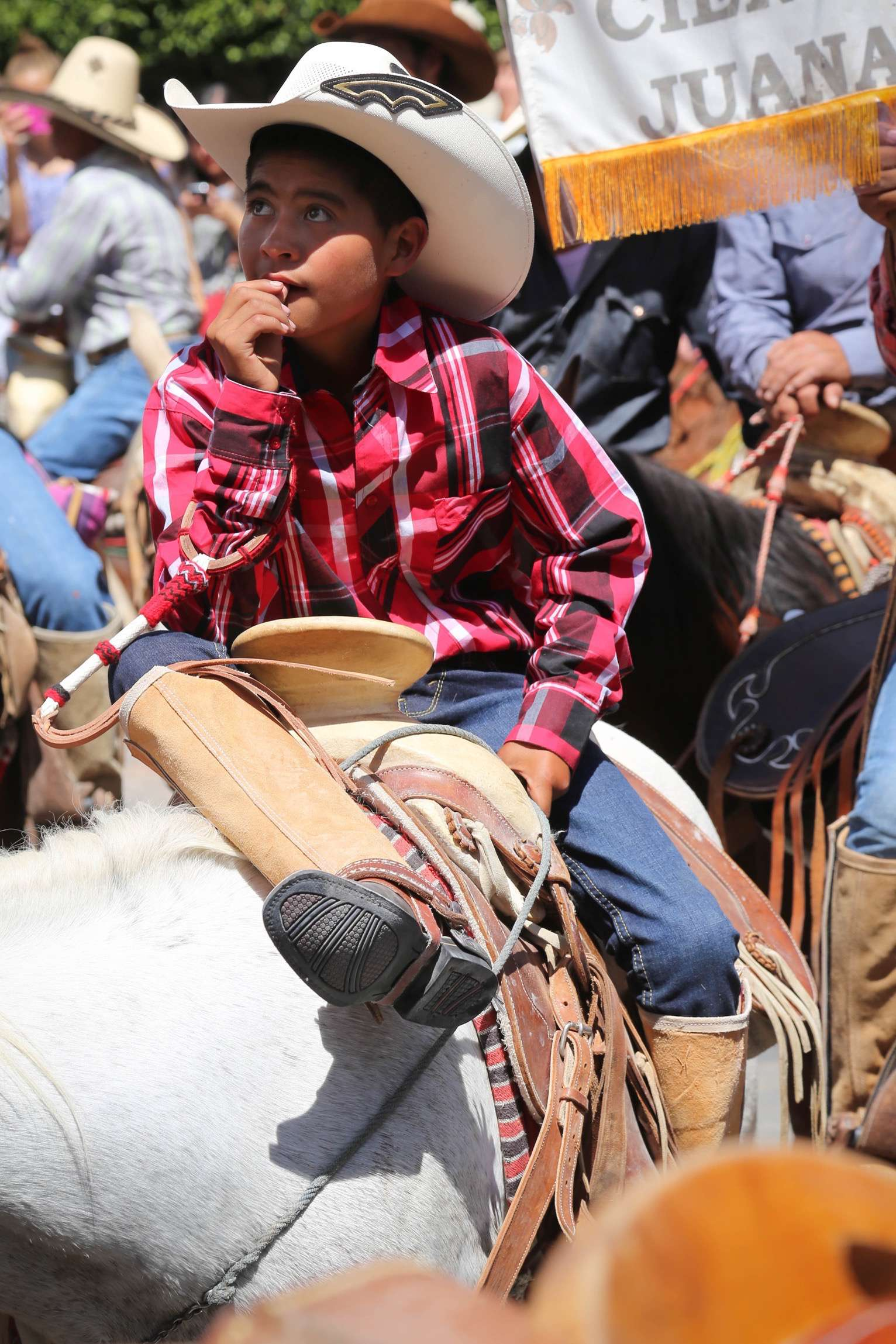 A young rider listens during the mass in the square at San Miguel de Allende.