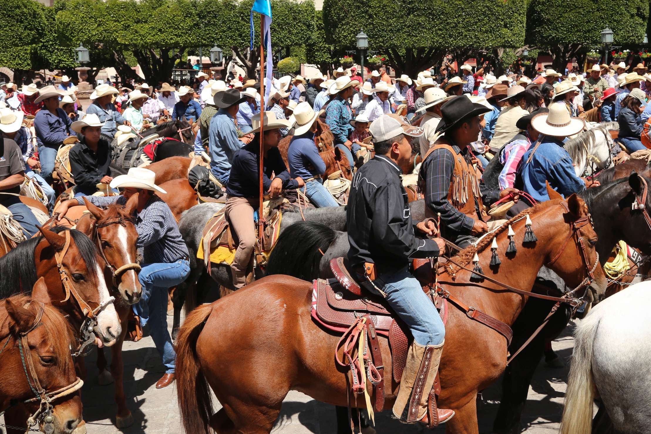Hundreds of horse riders pack into the square and participate in a mass in front of the church.
