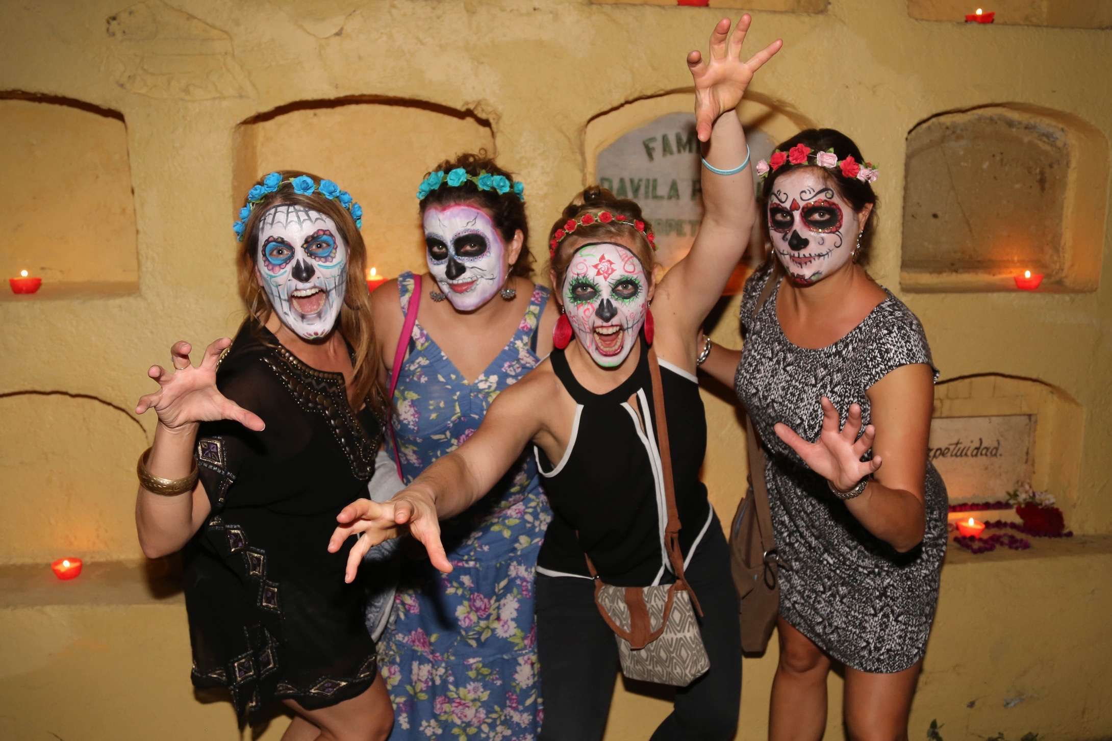 A group of face-painted tourists vamp at Oaxaca city's Panteon General cemetery during Dis de los Muertos.
