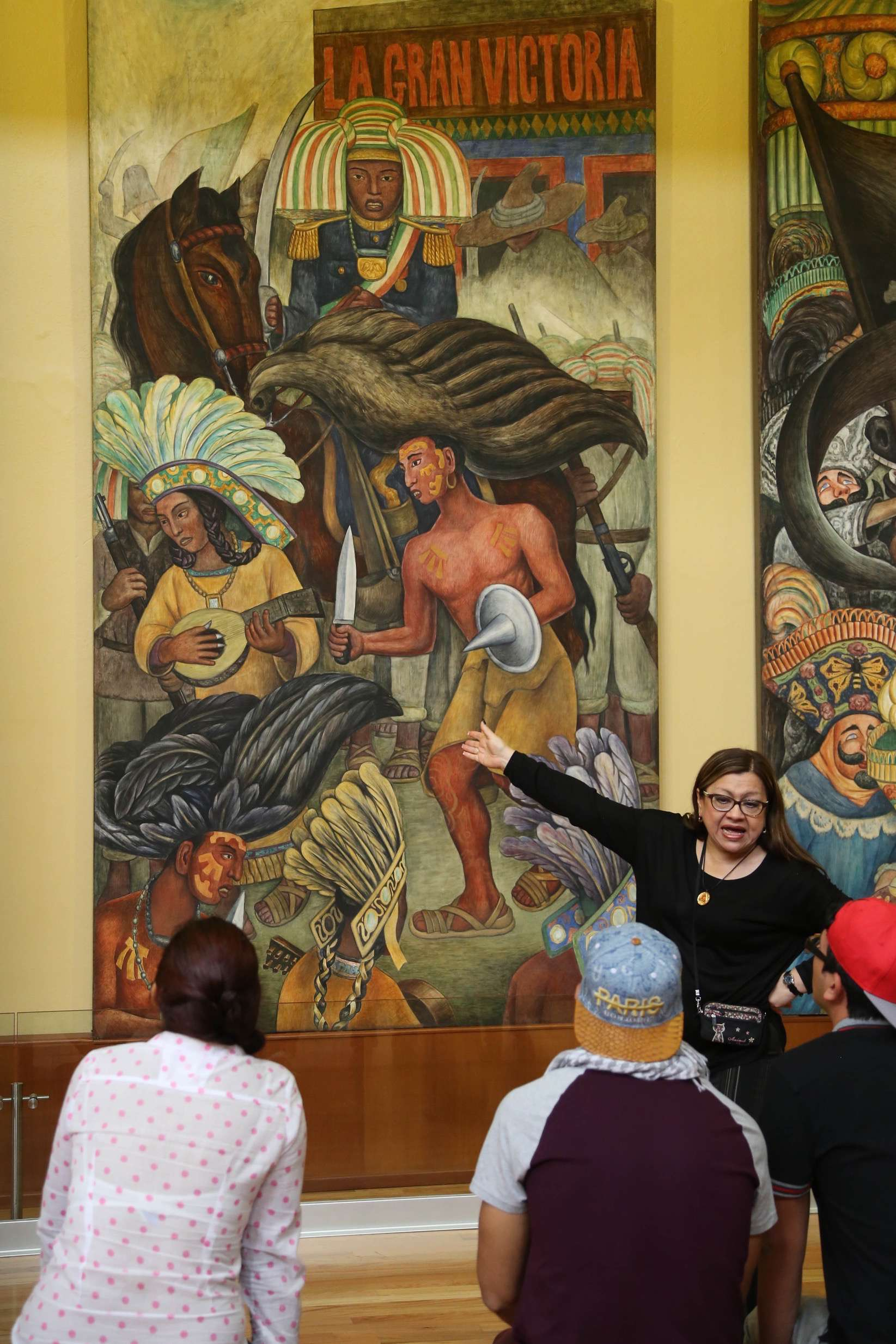 Visitors to Bellas Artes listen as the meaning of one of the murals is explained.