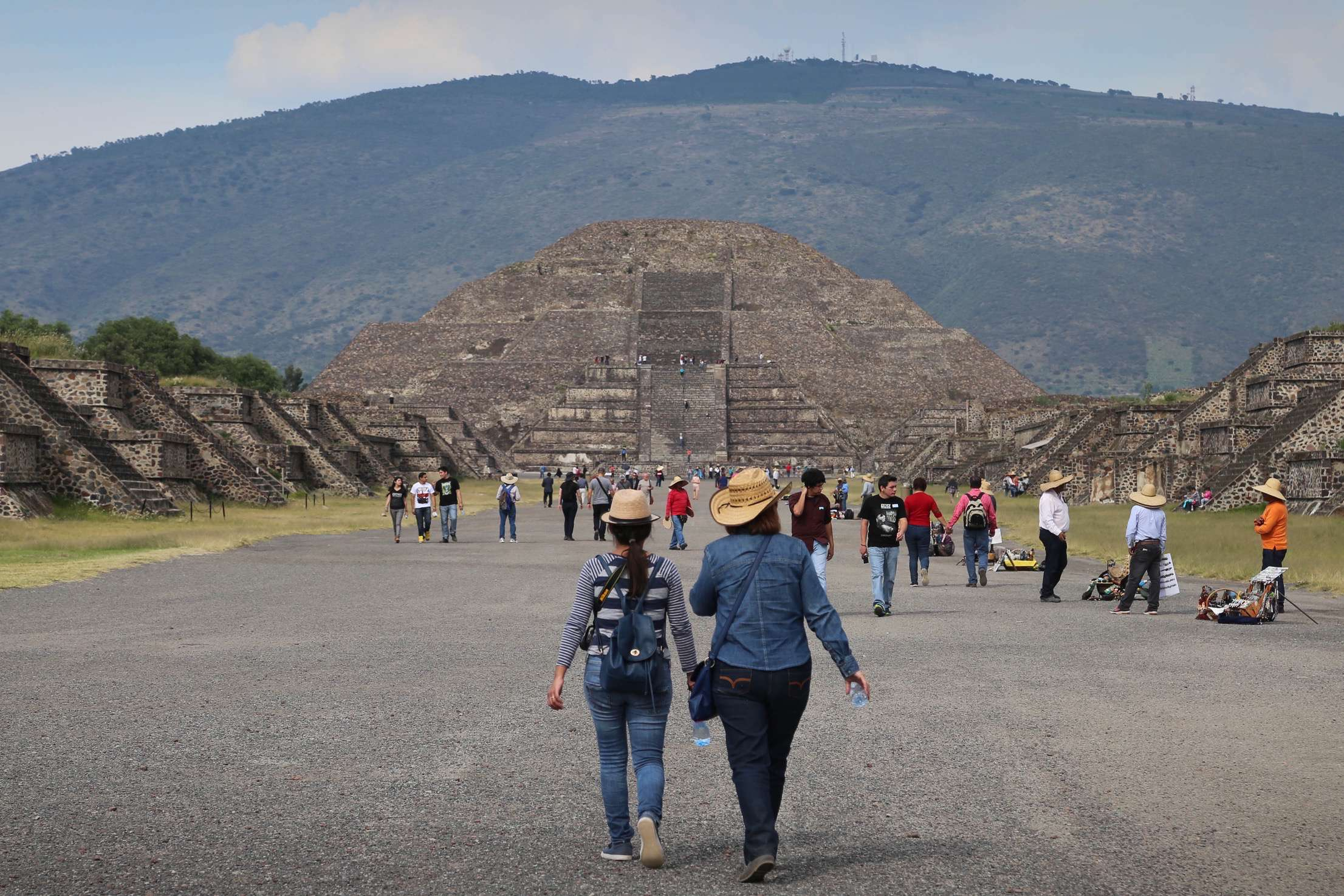 A pair of visitors stroll along the Avenue of the Dead on their way to inspect the Pyramid of the Moon as they approach a gauntlet of vendors, hawking trinkets.