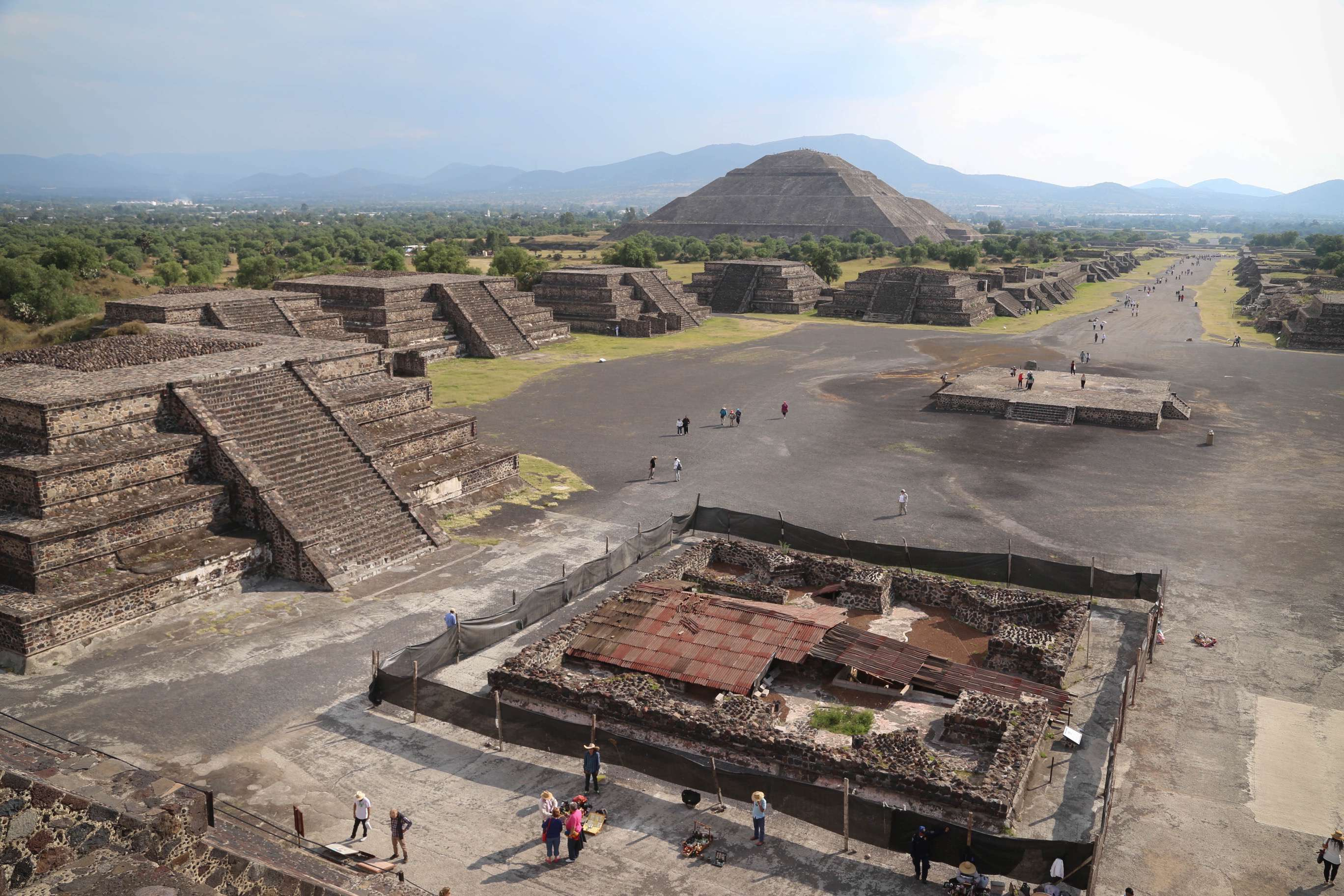 The Avenue of the Dead runs off to the right, the Pyramid of the Sun looms in the background and some of the building at Teotihuacan are arrayed along the boulevard.
