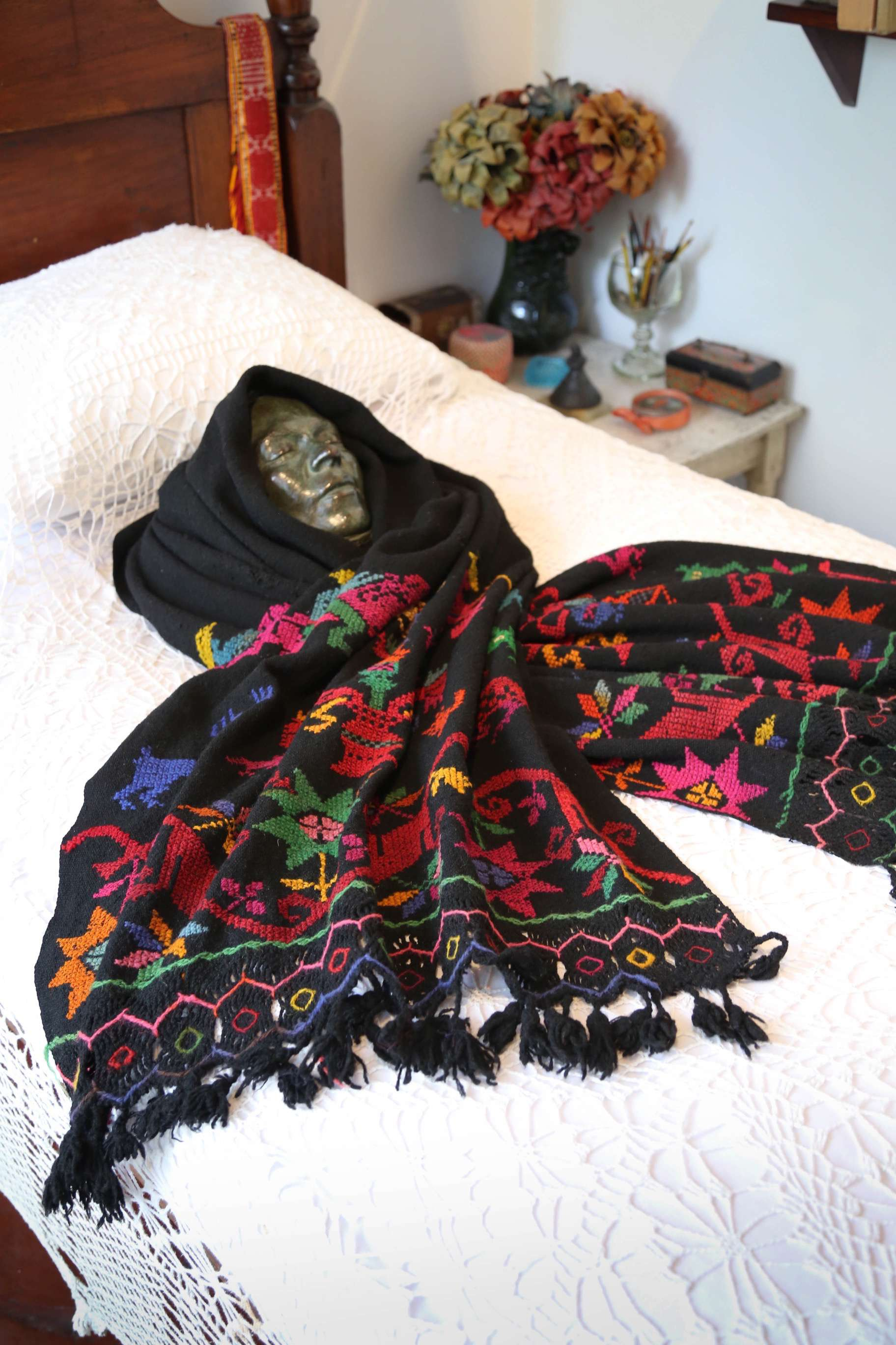 Frida Kahlo painted while lying in this bed and her mother had a mirror installed on the ceiling so Frida could paint self-portraits. Her death mask is draped in a shawl.