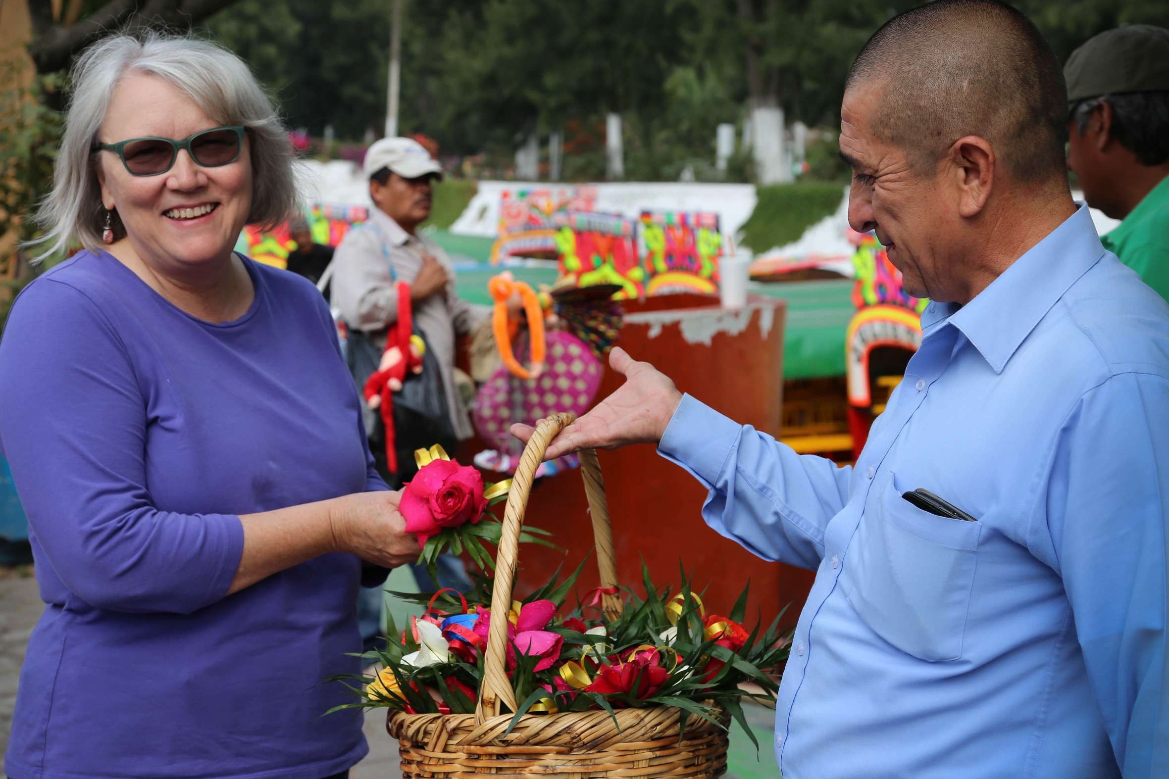 A vendor offers flowers to a visitor before she boards her trajinera.