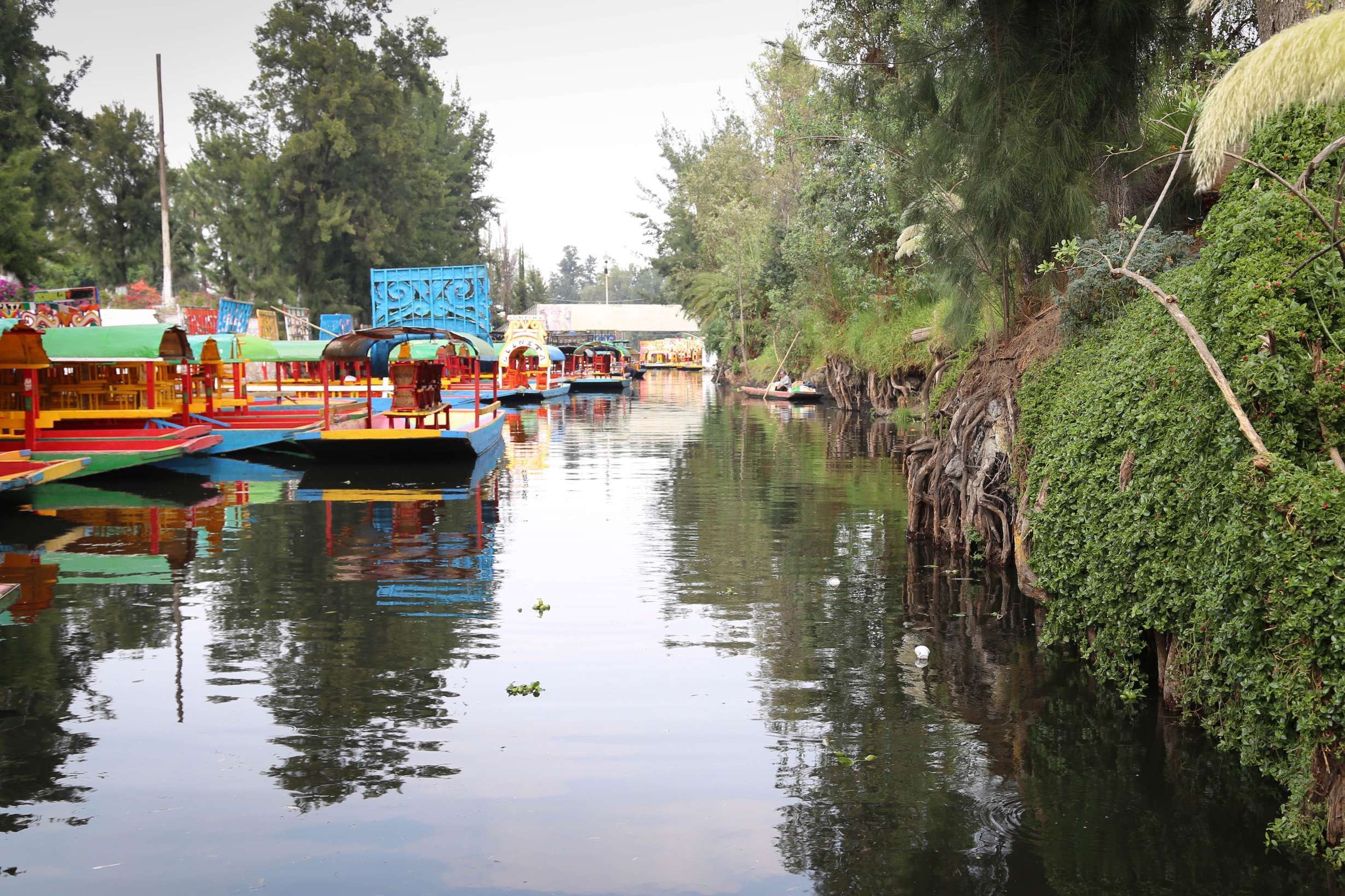 Trajineras are poled along the canals at Xochimilco as visitors relax and while away an afternoon.
