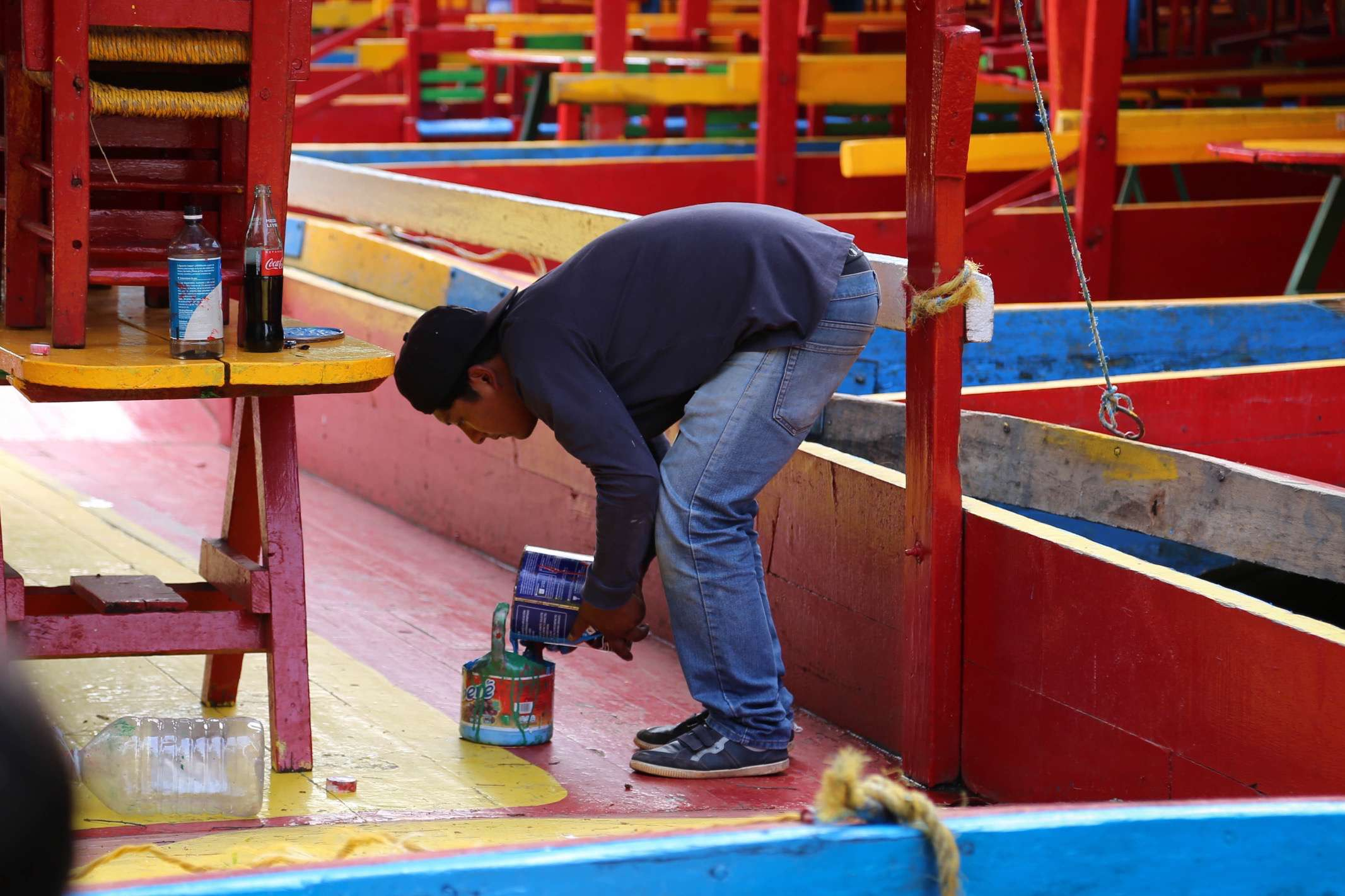 A worker readies some paint to apply to his trajinera.