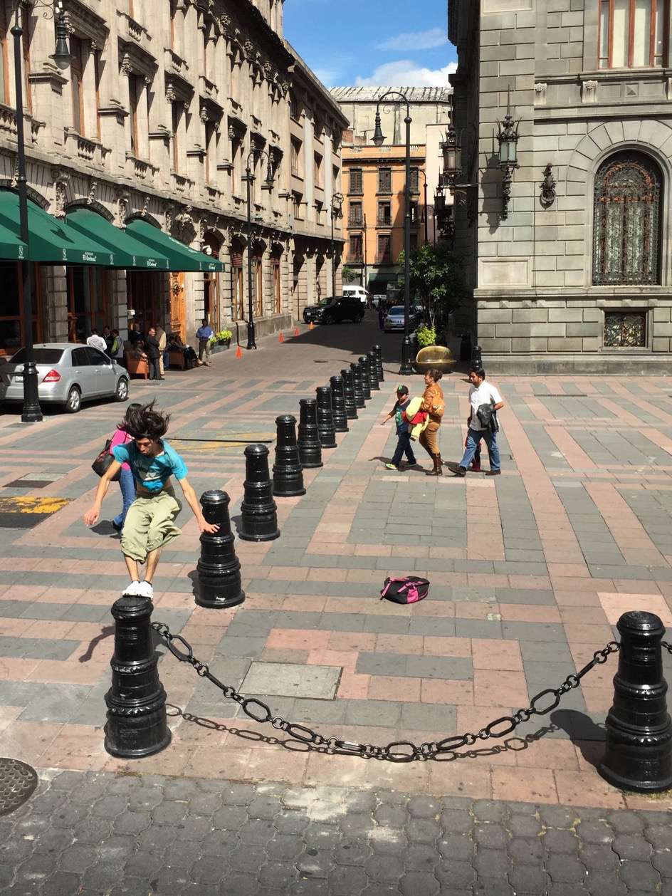 A street performer nails the landing atop a barrier, earning tips from drivers stopped at a light.