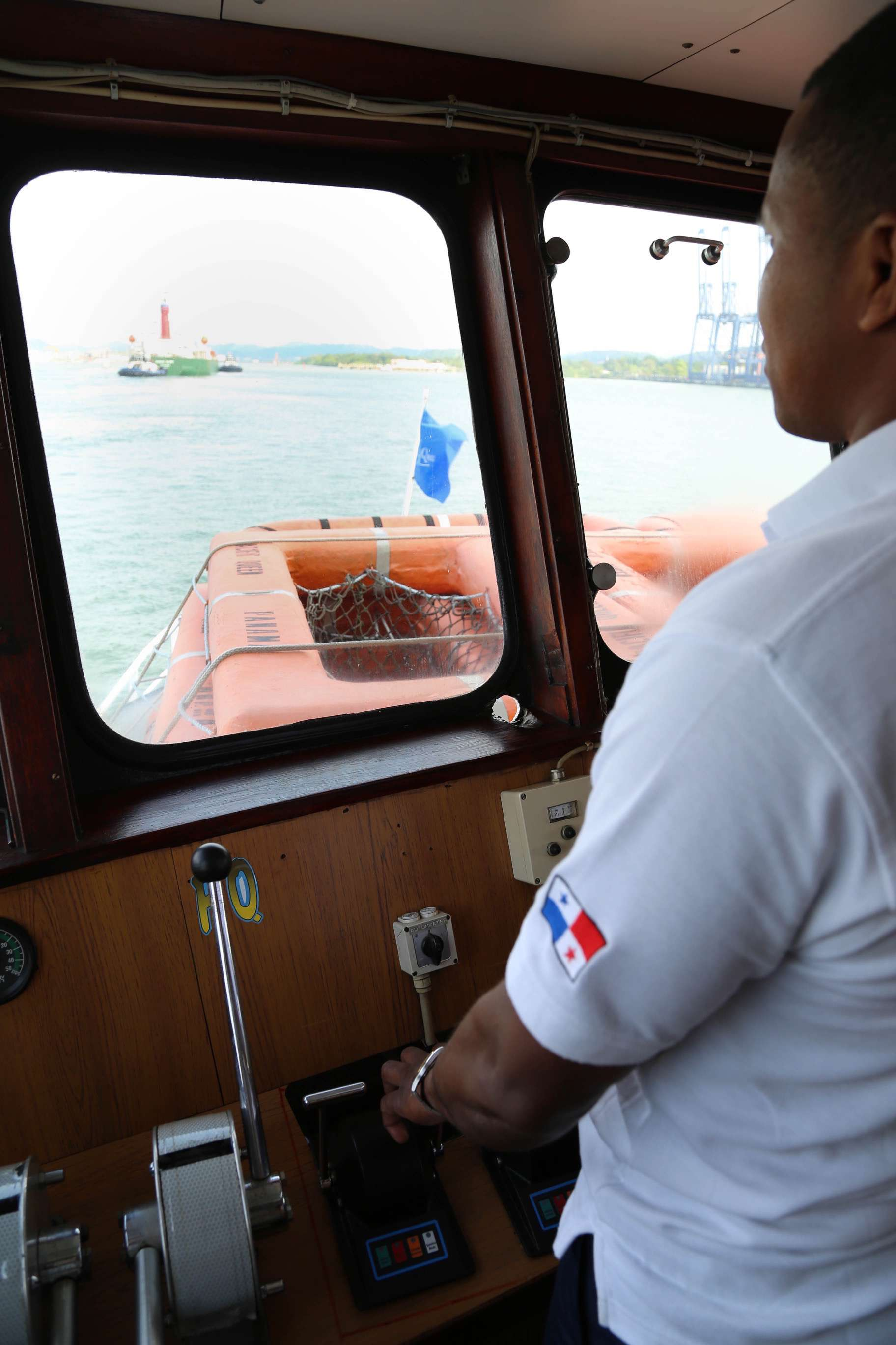 The captain carefully guides his ship along the Panama Canal while the canal pilot watches from a station in the wheelhouse.