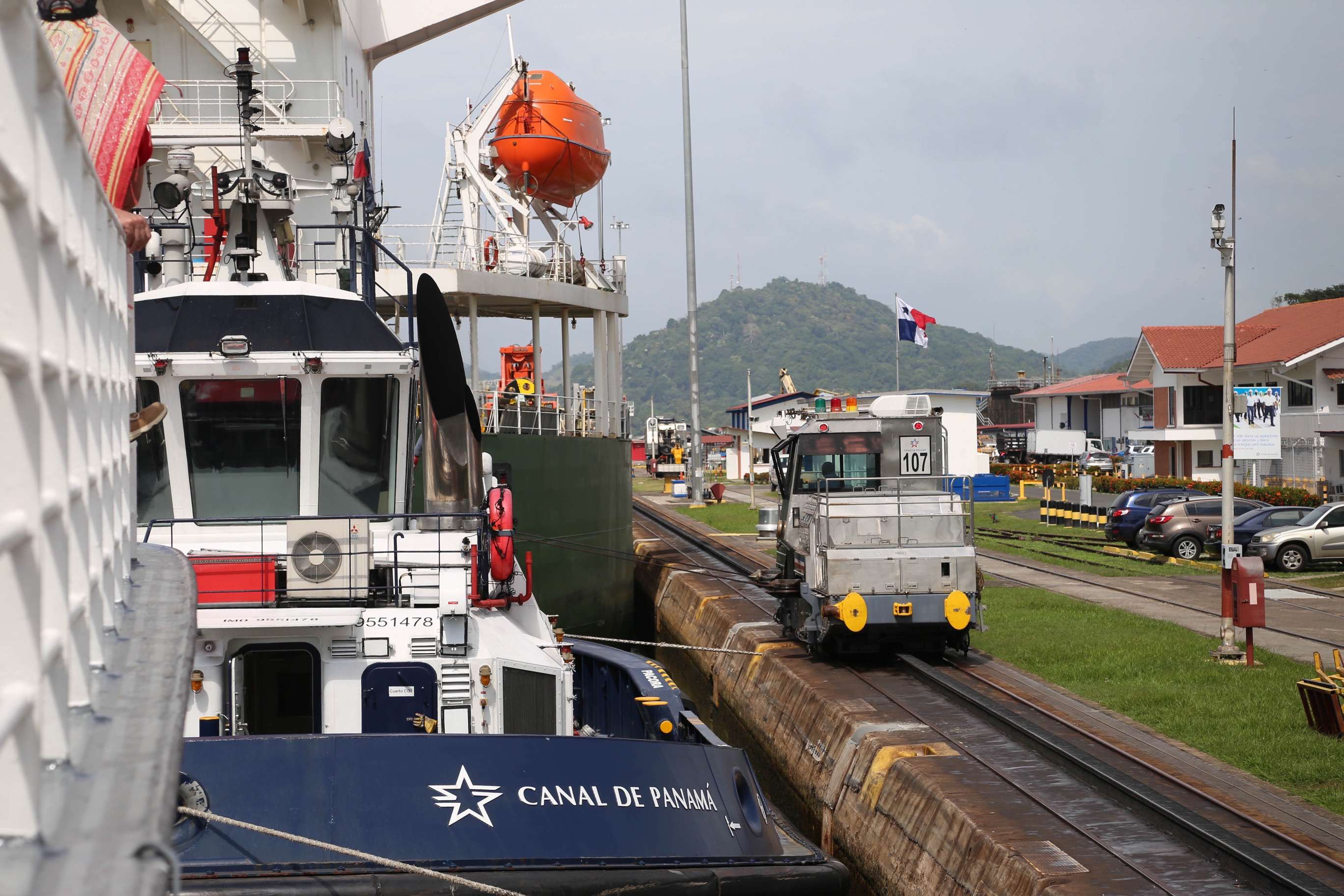 Locomotives, one at the bow, the other at the stern, run along side each side of the locks at the Panama Canal to carefully transport larger vessels up, down and through the six locks required to transit the entire canal.