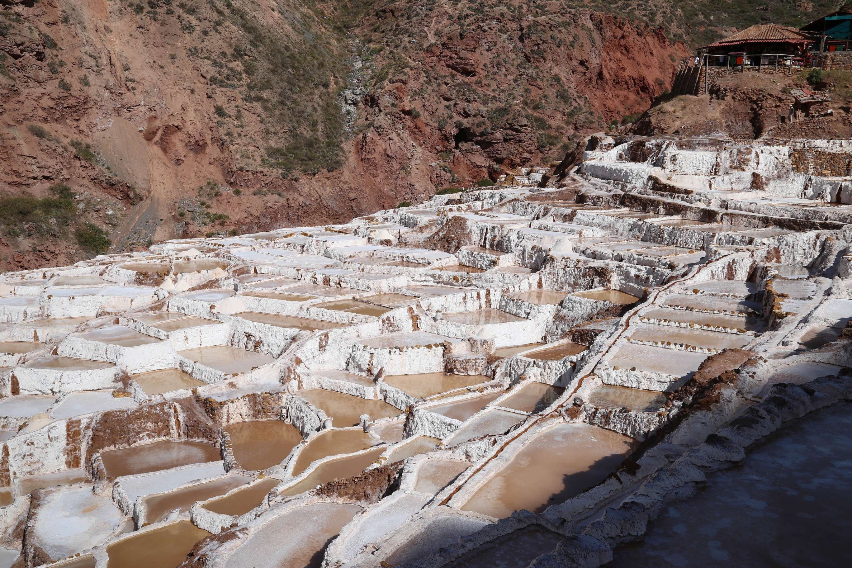 Before visitors get a chance to walk through the salt works, they pass by the vendors, top right, who sell small packet of salt from Maras, Peru.