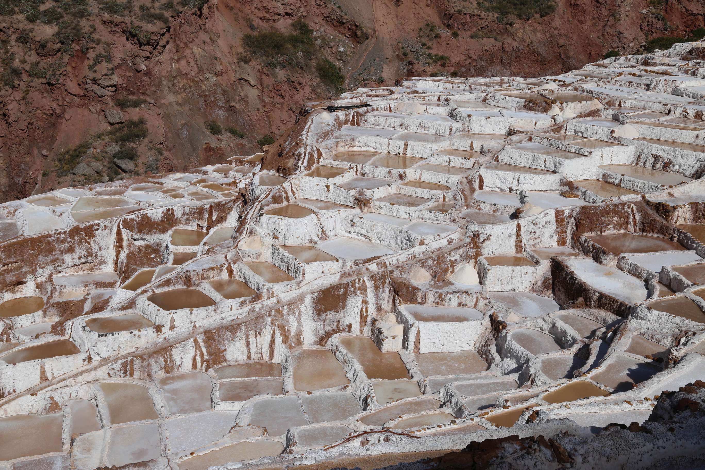 What might appear to be a hodge-podge of disorganization are carefully established ponds to produce salt at Maras, Peru. Note the small channels that carry brine to each pond.