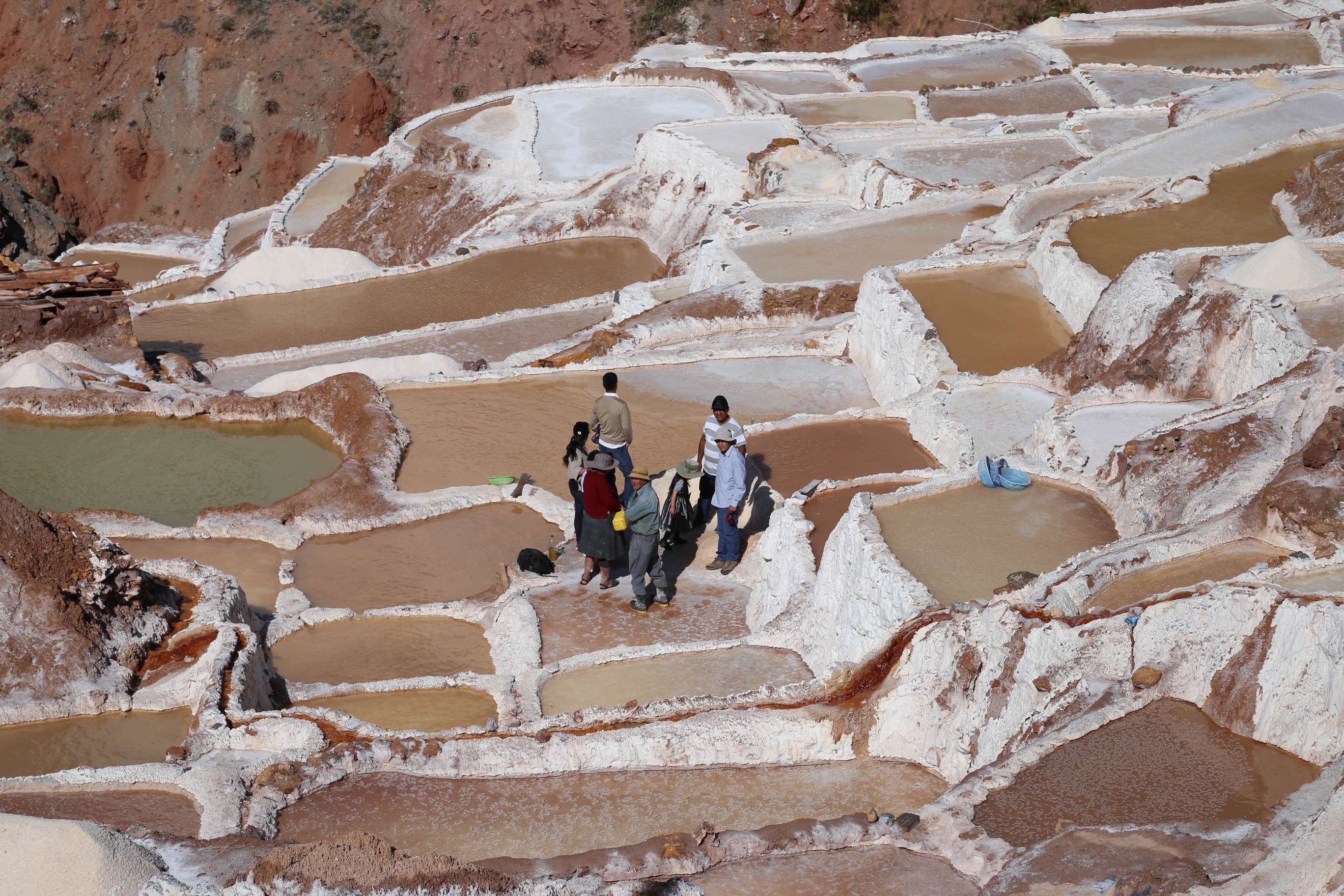 A group of salt producers looks over their ponds, gauging how much longer to harvest.