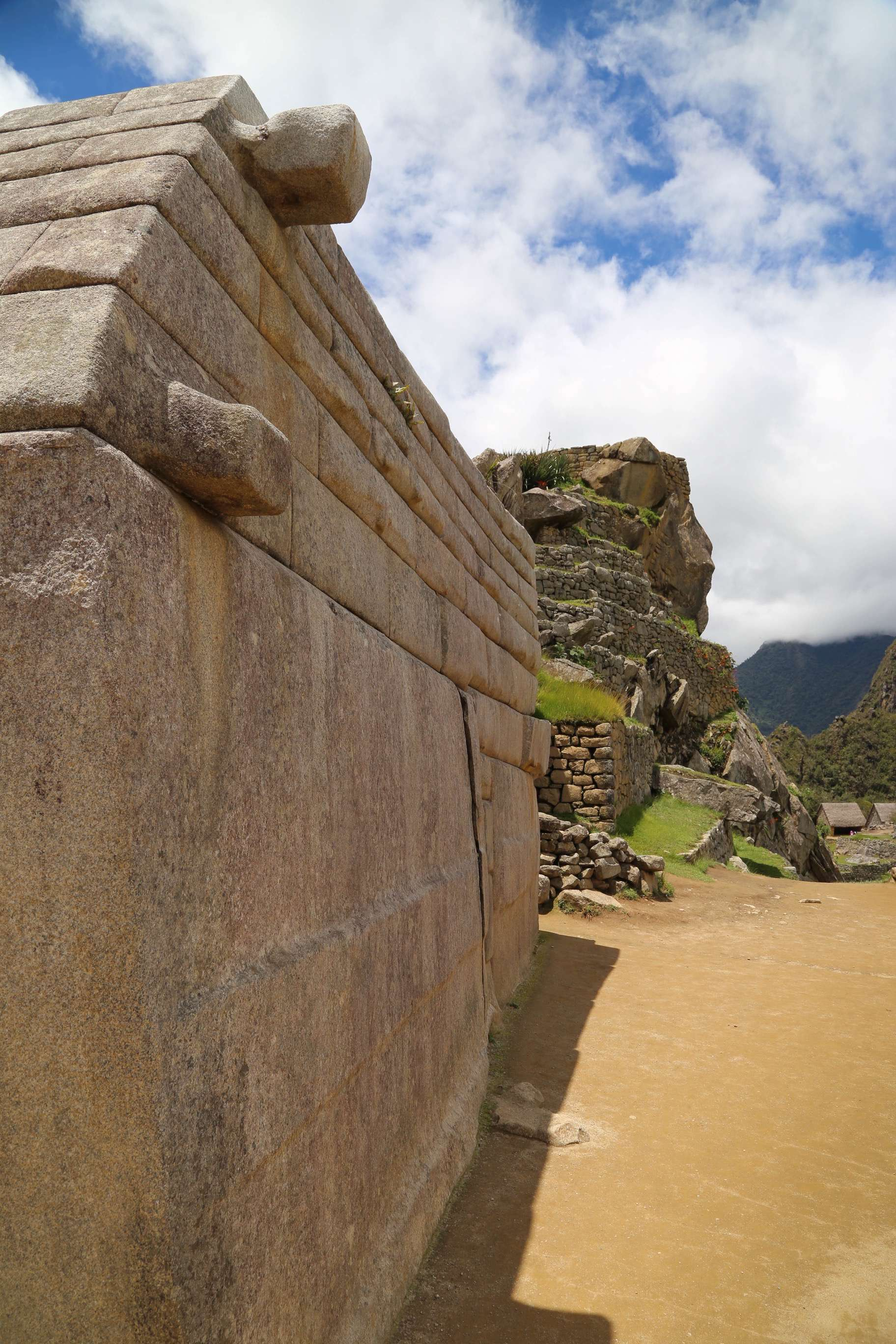 The precision of Inca stone work can be seen on the wall at the left, where even to this day the fitting is so tight the blade of a knife cannot be inserted between stones.