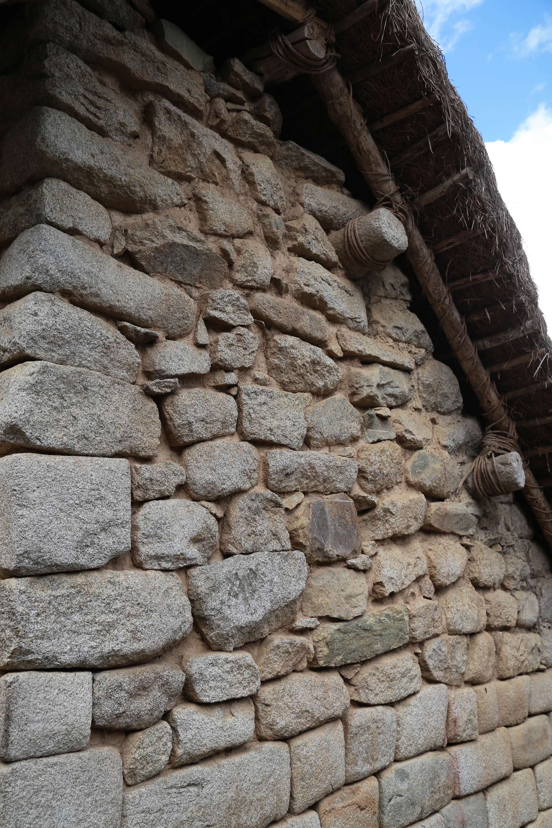 This restored building shows how timbers and roofing material were secured and provided a dry space for people to live and to store food.