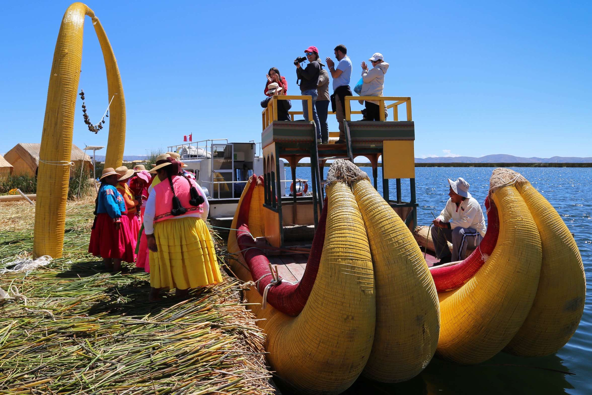 A group of visitors board a reed-built boat for a short jaunt on Lake Titicaca.
