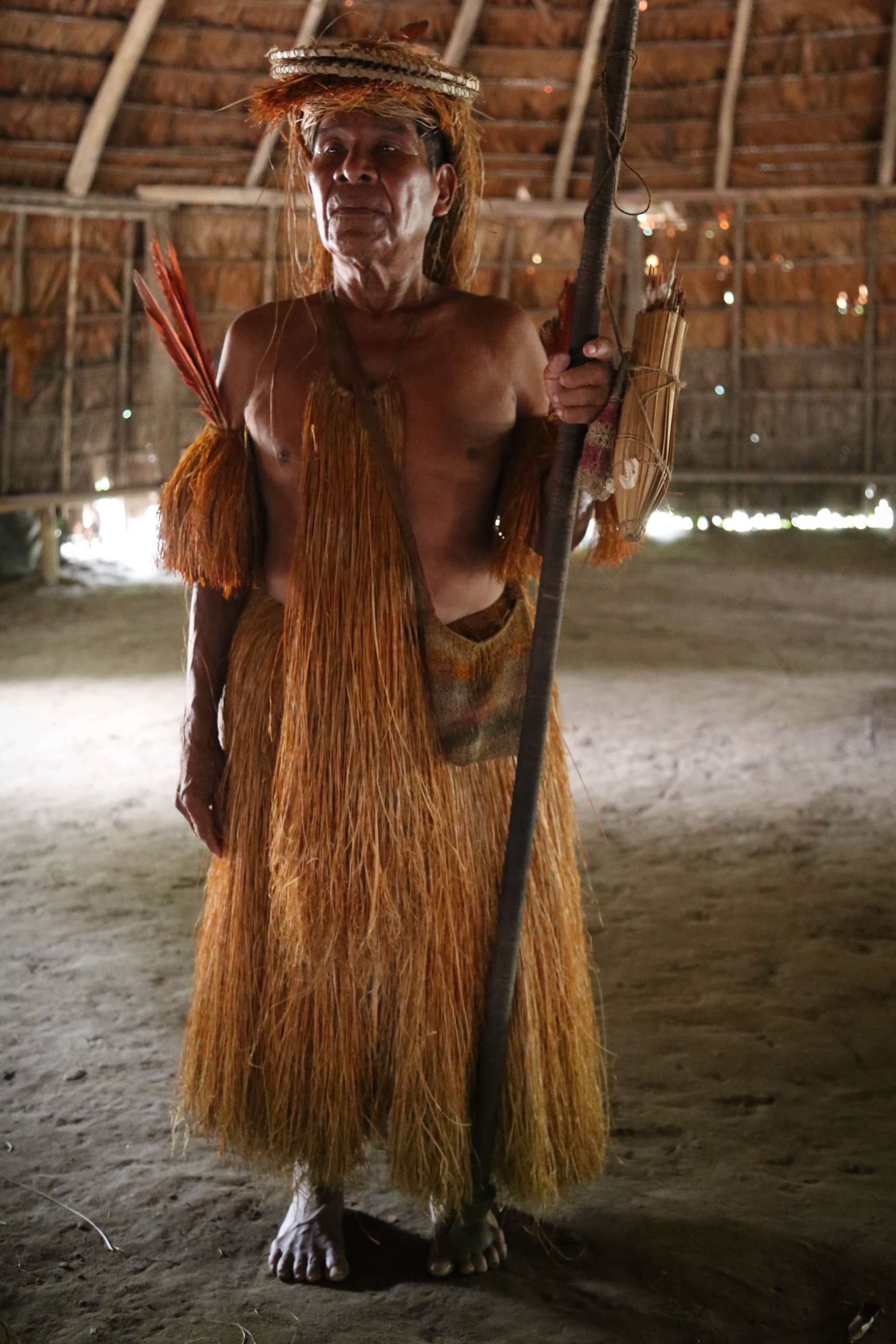 This older man, a Yagua, stands in the group's main hut and displays his traditional garb and hunting weapon -- a blowgun and darts. Spanish conquerors thought the men were women and named the area Amazon, after the ancient female warriors.