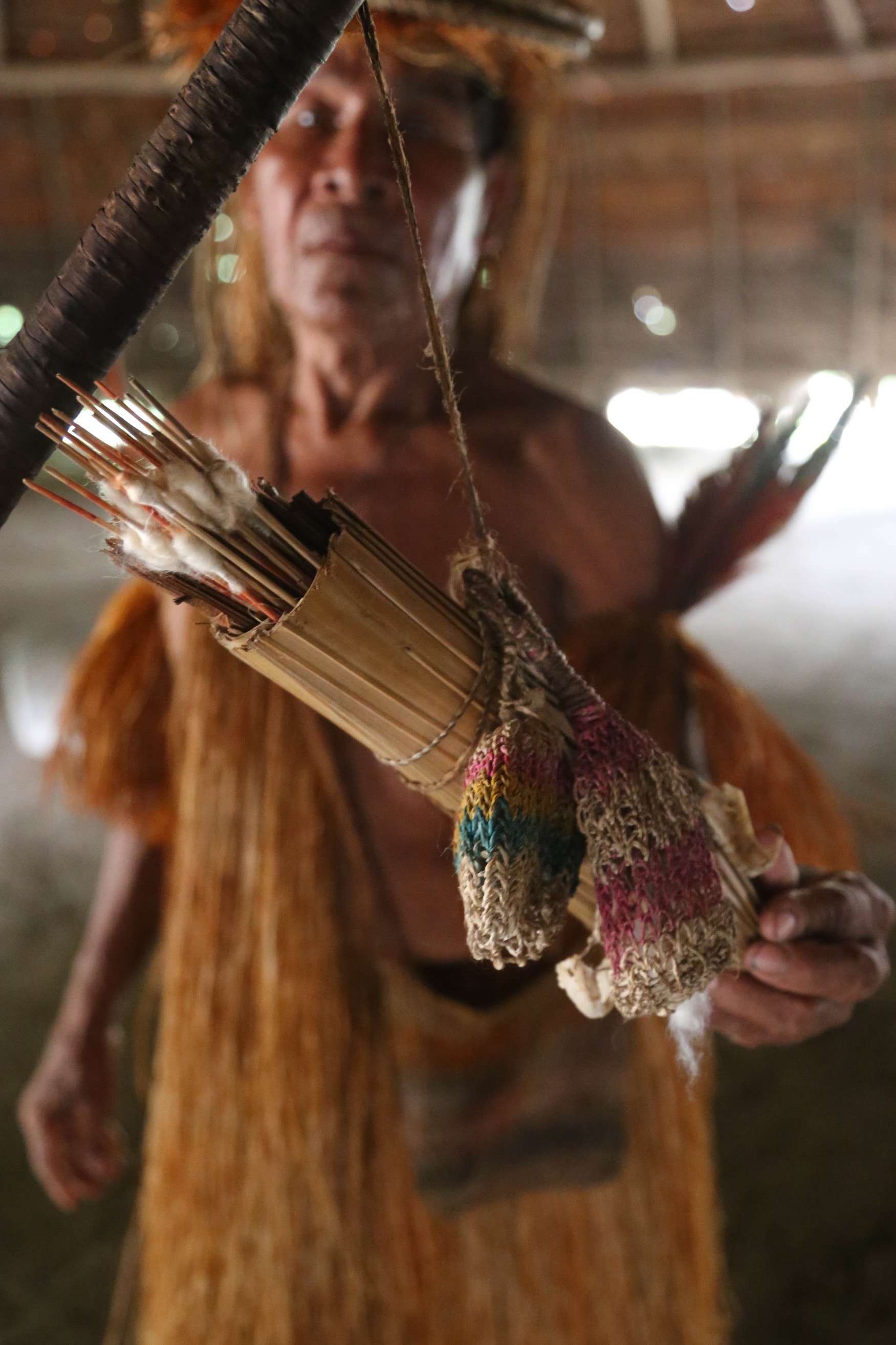 A quiver of darts rests in its holder that dangles from a Yagua's blowgun.