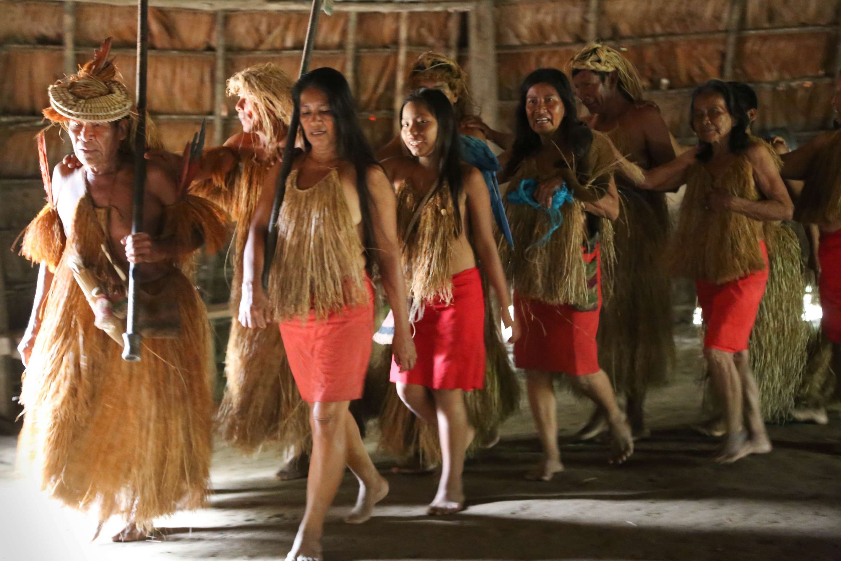 Men and women dance together. The men wear a grass skirt and the women usually wear a red cloth skirt.