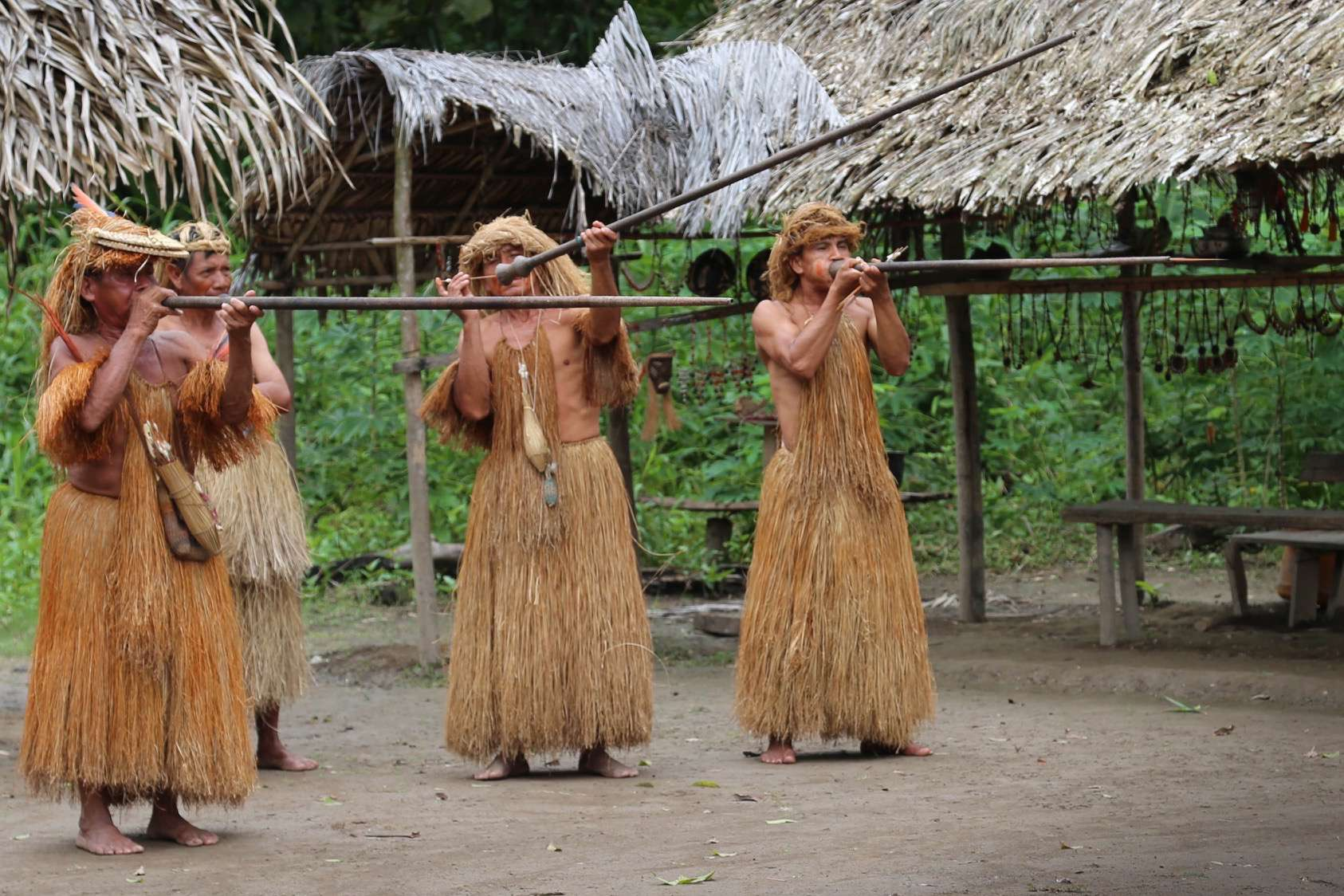 "This trio of Yagua men show off a ""ready, aim, fire"" of darts. Note the dart coming out of the end of the blowgun on the right."