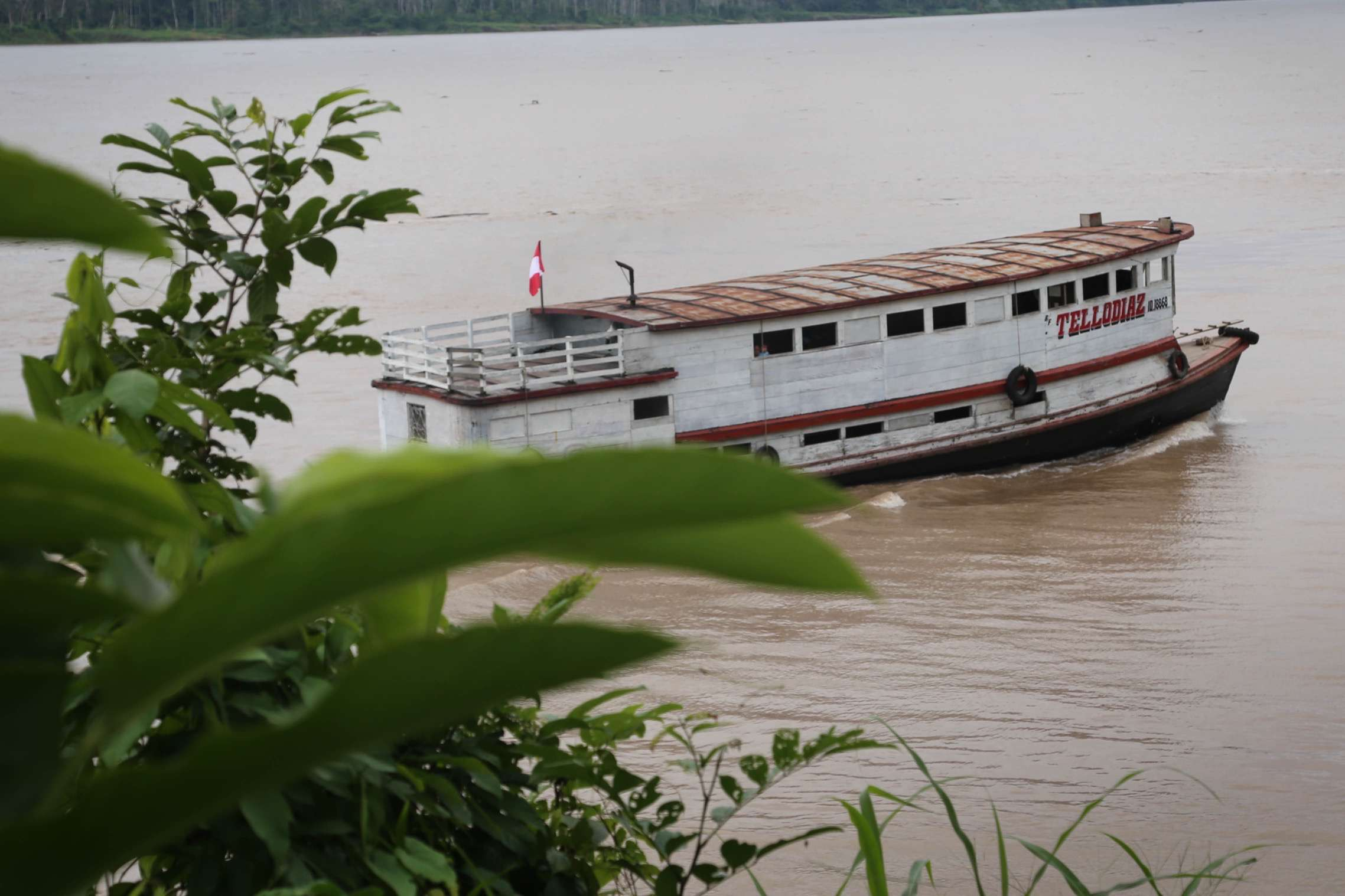 A water taxi plies the river, transporting people and cargo.